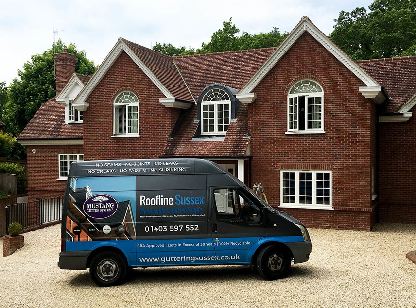 A recently installed Mustang Gutter system on a large property. The Roofline Sussex van is parked in front.