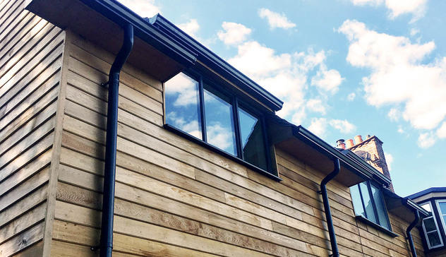 Stylish black aluminium guttering on a wooden-clad domestic property.