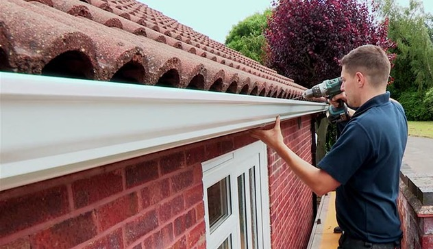 White seamless gutter being installed by a Mustang approved installer.