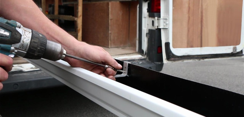 Internal brackets being fitted to an aluminium seamless gutter.